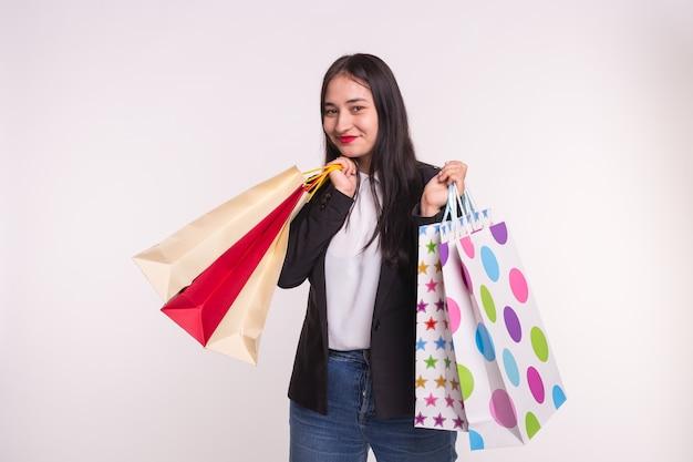 Porträt der jungen glücklichen brünetten frau mit einkaufstüten auf weiß