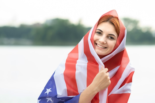 Porträt der jungen glücklichen flüchtlingsfrau mit usa-nationalflagge auf kopf und schultern
