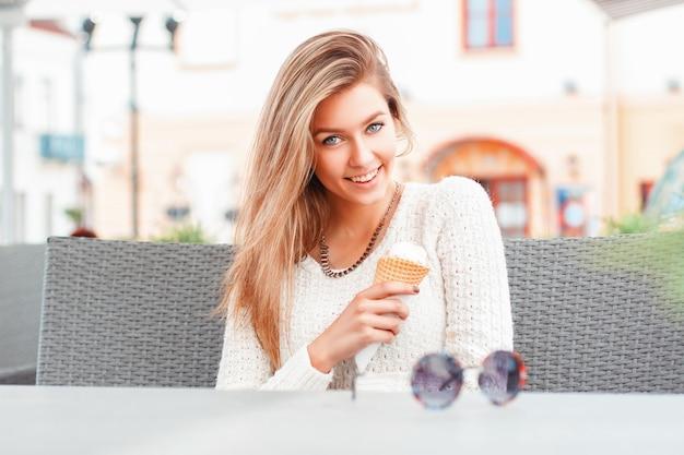 Porträt der jungen glücklichen frau, die eis im freien isst
