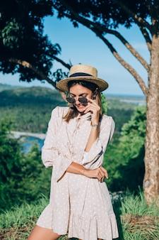 Porträt der jungen glücklichen frau im sommerkleid, in der sonnenbrille und im strohhut