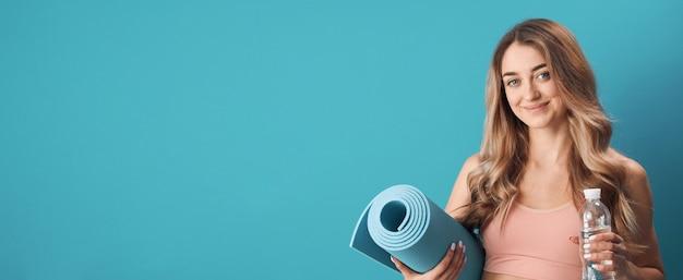 Porträt der jungen glücklichen frau im sport-bh, der übungsmatte und wasser-, sport- und gesundheitskonzept hält