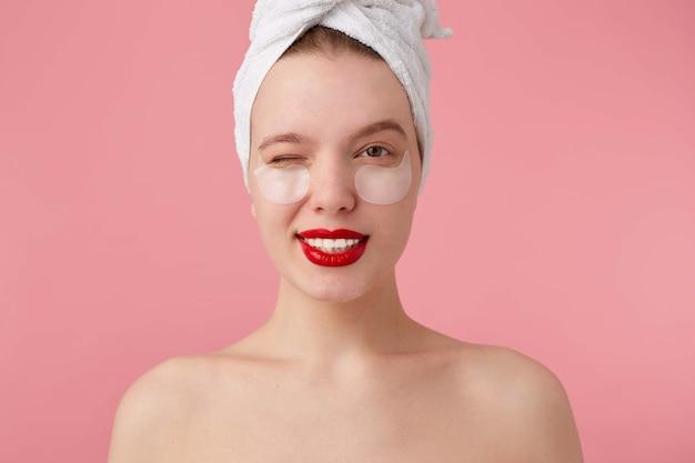 Porträt der jungen glücklichen frau nach dem duschen mit einem handtuch auf ihrem kopf, mit flecken und roten lippen, schauend und zwinkernd.