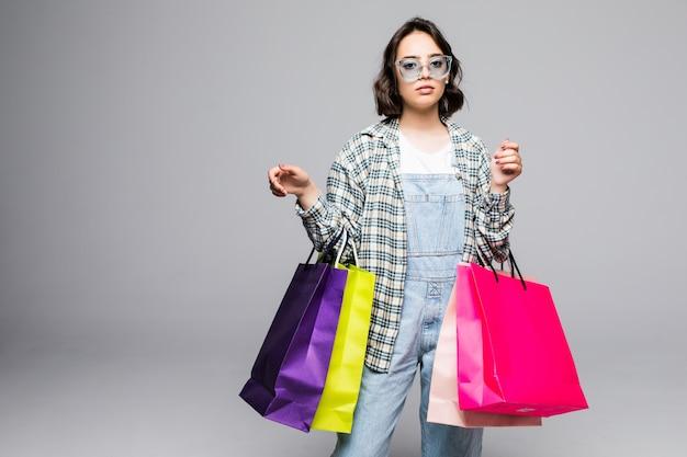 Porträt der jungen glücklichen lächelnden frau in der sonnenbrille mit einkaufstüten lokalisiert auf grau. verkaufskonzept.