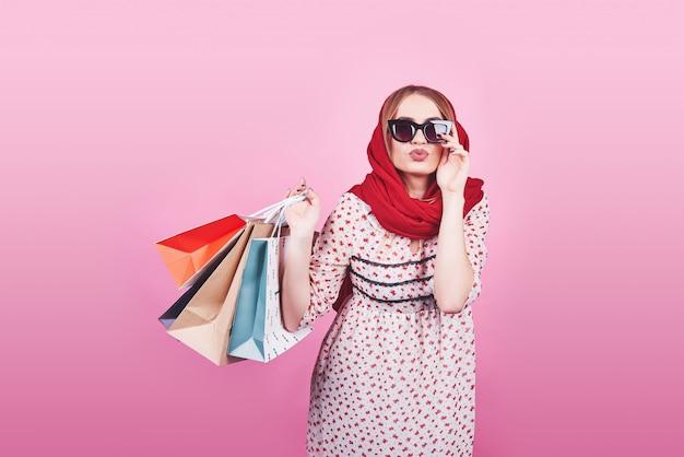 Porträt der jungen glücklichen lächelnden frau mit einkaufstaschen auf rosa
