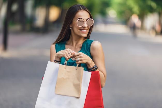 Porträt der jungen glücklichen lächelnden frau mit einkaufstaschen genießend beim einkaufen