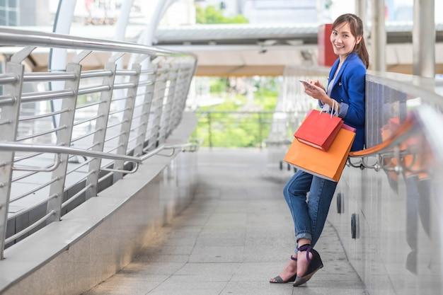 Porträt der jungen glücklichen lächelnden frau mit einkaufstaschen