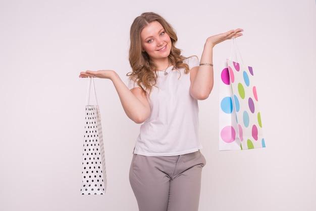 Porträt der jungen glücklichen lächelnden frau mit einkaufstüten auf weiß.