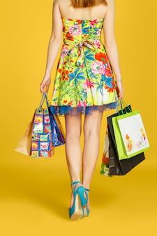 Porträt der jungen glücklichen lächelnden frau mit einkaufstüten gegen gelbe wand