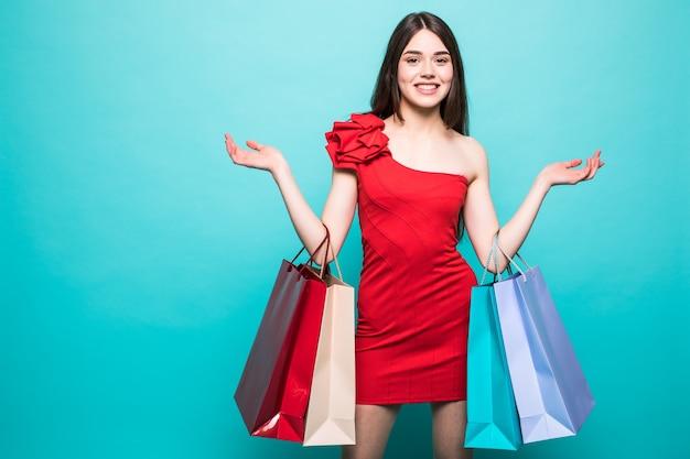 Porträt der jungen glücklichen lächelnden frau mit einkaufstüten lokalisiert