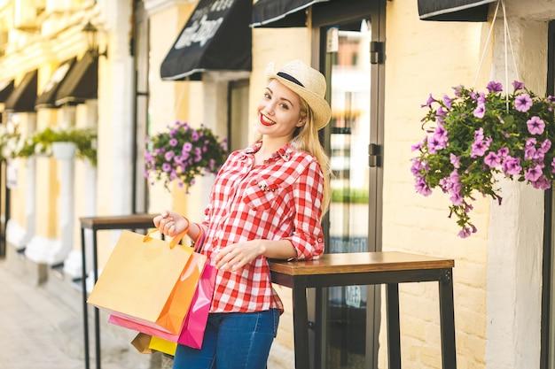 Porträt der jungen glücklichen lächelnden frau mit einkaufstüten