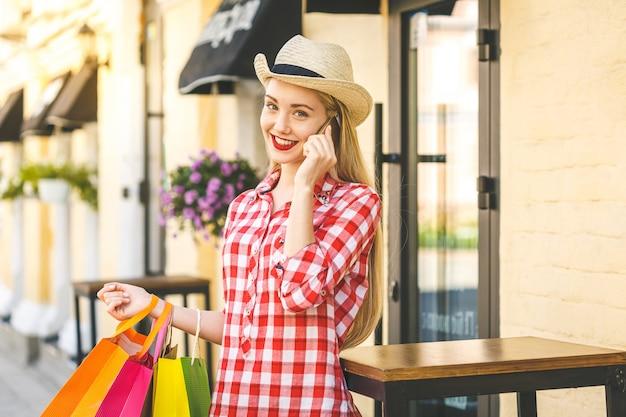 Porträt der jungen glücklichen lächelnden frau mit telefon. junge frau, die einkaufstaschen hält. online-shopping-konzept