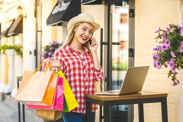 Porträt der jungen glücklichen lächelnden frau mit telefon. junge frau, die einkaufstaschen hält und laptop-computer verwendet. online-shopping-konzept