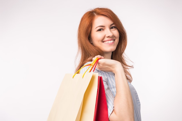 Porträt der jungen glücklichen lächelnden rothaarigen frau mit einkaufstüten auf weiß.