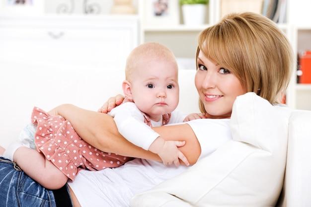 Porträt der jungen glücklichen mutter mit neugeborenem baby zu hause
