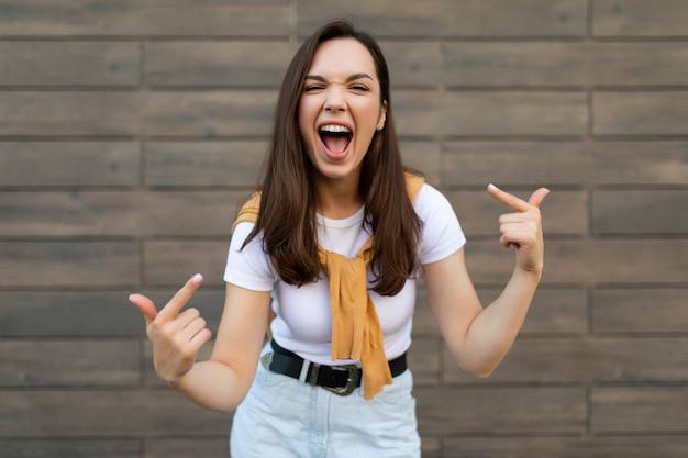 Porträt der jungen glücklichen positiven schönen brünetten frau mit aufrichtigen gefühlen, die stilvolles trägt