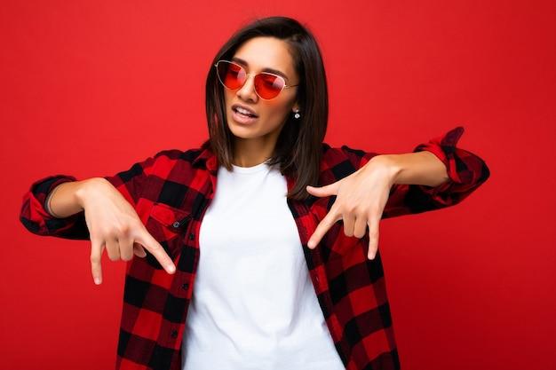 Porträt der jungen glücklichen positiven schönen brunettefrau mit aufrichtigen gefühlen, die weißes t-shirt, stilvolles rotes karohemd und rote sonnenbrille einzeln auf rotem hintergrund mit kopienraum tragen.