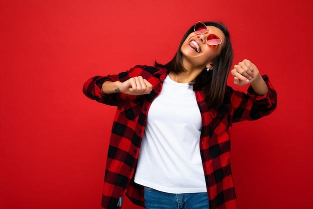 Porträt der jungen glücklichen positiven schönen brunettefrau mit aufrichtigen gefühlen, die weißes t-shirt tragen