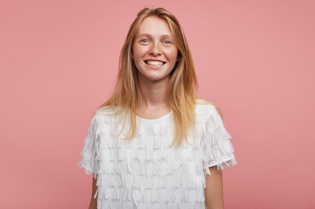 Porträt der jungen glücklichen reizenden rothaarigen frau mit lässiger frisur, die ihre weißen perfekten zähne zeigt, während fröhlich lächelnd, gegen rosa hintergrund stehend