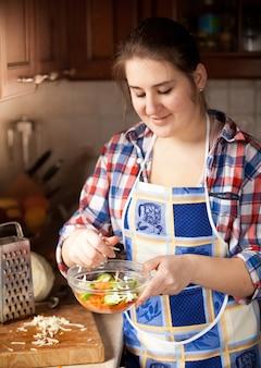Porträt der jungen hausfrau, die salat mit gurken zubereitet