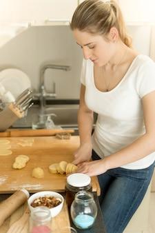 Porträt der jungen hausfrau, die teig auf küche macht