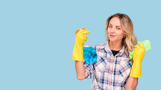 Porträt der jungen hausmeisterfrau, die reinigungsmittelsprühflasche und -serviette hält