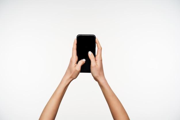 Porträt der jungen hellhäutigen hübschen hände, die schwarzes modernes smartphone halten, während sie auf weiß posieren und daumen auf bildschirm halten