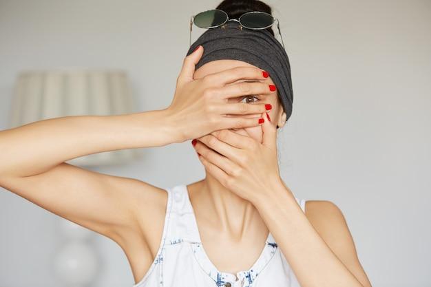 Porträt der jungen hipsterfrau, die durch ihre finger guckt
