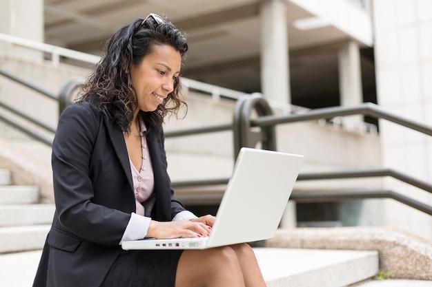 Porträt der jungen hispanischen frau, die sich mit einem laptop konzentriert. sie sitzt auf der straße.