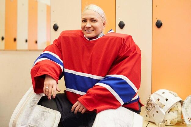Porträt der jungen hockeyspielerin, die an der kamera lächelt