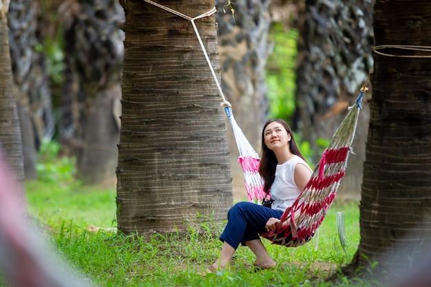 Porträt der jungen hübschen asiatin, die auf hängematte im arengapalmenwald sich entspannt.