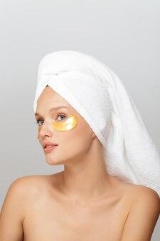 Porträt der jungen hübschen dame mit weißem handtuch auf kopf mit gelben flecken unter den augen