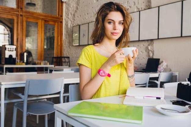 Porträt der jungen hübschen frau, die am tisch im café sitzt kaffee trinkt, tasse in den händen hält, studentenlernen, bildung