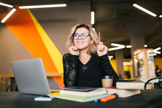 Porträt der jungen hübschen frau, die am tisch im schwarzen hemd sitzt und am laptop im mitarbeitenden büro arbeitet