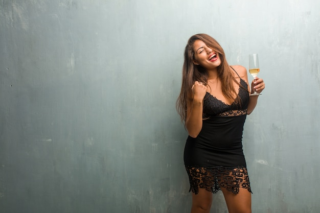 Porträt der jungen hübschen frau, die ein kleid gegen eine wand sehr glücklich und aufgeregt trägt
