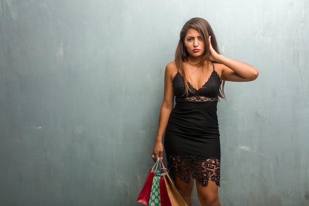 Porträt der jungen hübschen frau, die ein kleid gegen ohren einer wandbedeckung mit den händen trägt