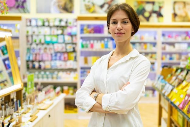 Porträt der jungen hübschen frau in der weißen bluse steht im kosmetikshop