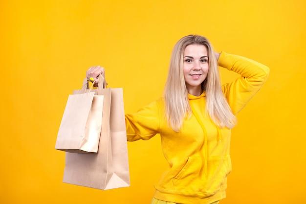 Porträt der jungen hübschen kaukasischen blonden frau mit papieröko-taschen im gelben sportanzug, lokalisiert