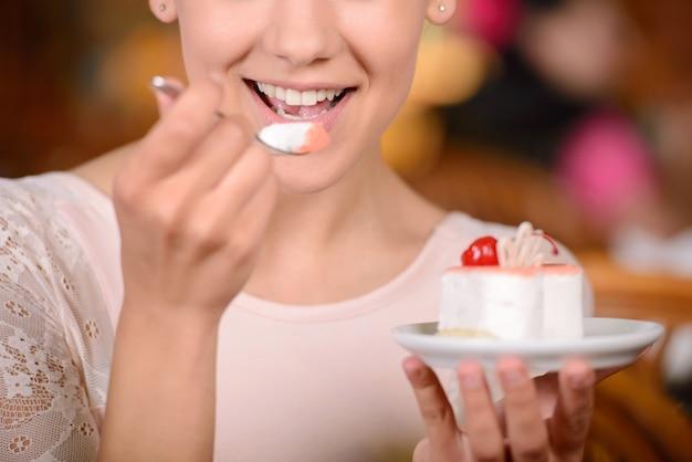Porträt der jungen hübschen lächelnden frau, die kuchen isst.