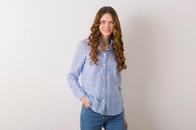 Porträt der jungen hübschen natürlichen frau, die im blau gestreiften baumwollhemd gegen weiß aufwirft