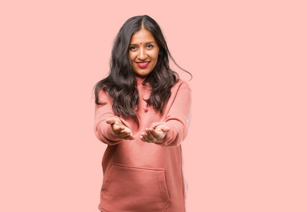 Porträt der jungen indischen frau der eignung, die etwas mit den händen hält, ein produkt zeigt, lächelnd und nett, einen eingebildeten gegenstand anbietend