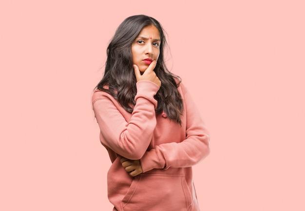 Porträt der jungen indischen frau der eignung, die oben, verwirrt über eine idee denkt und schaut, würde versuchen, eine lösung zu finden