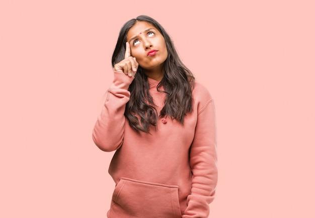 Porträt der jungen indischen frau der eignung, die oben, verwirrt über eine idee denkt und schaut