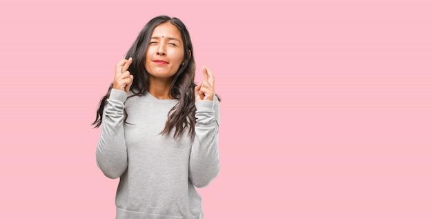 Porträt der jungen indischen frau, die seine finger kreuzt, möchte für zukünftiges projekt glücklich sein