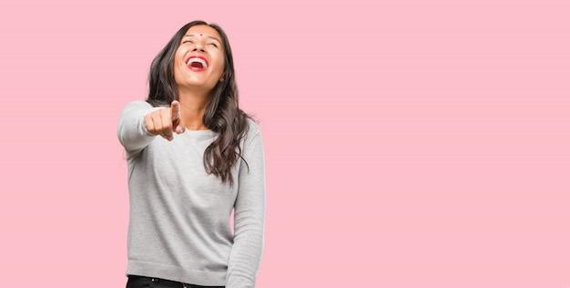 Porträt der jungen indischen frau, die von anderen, konzept der spott und unkontrollierung schreit, lacht und sich über sie lustig macht