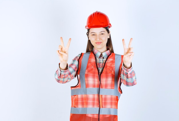 Porträt der jungen ingenieurin im helm, die victory-zeichen gibt.