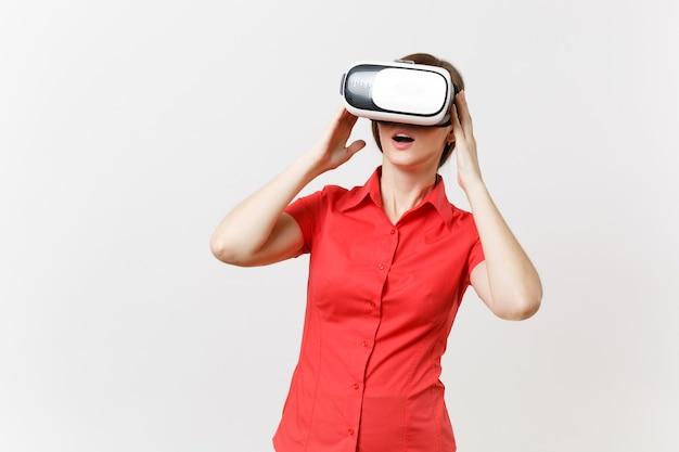 Porträt der jungen intelligenten geschäftsfrau im roten hemd, schwarzer rock im kopfhörer der virtuellen realität auf dem kopf lokalisiert auf weißem hintergrund. bildung oder lehre der zukunft im hochschulkonzept.