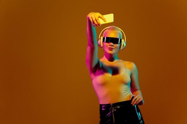 Porträt der jungen kaukasischen frau auf braunem hintergrund mit copyspace, ungewöhnlichem und ausgeflipptem aussehen