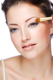 Porträt der jungen kaukasischen frau der schönheit, die kosmetik auf augenlid anwendet