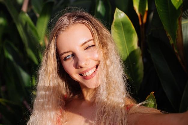 Porträt der jungen kaukasischen frau im roten passenden eleganten kleid im freien auf hintergrund der tropischen blätter