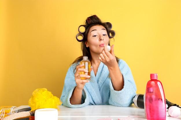 Porträt der jungen kaukasischen frau in ihrem schönheitstag, haut- und haarpflege-routine. weibliches modell mit naturkosmetik, die creme und öle für make-up aufträgt. körper- und gesichtspflege, natürliches schönheitskonzept.